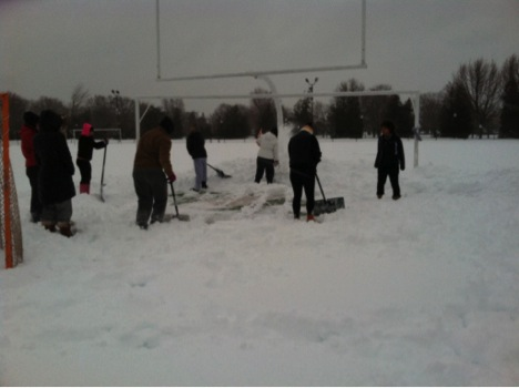 Women's lacrosse shoveling the turf at Jess Dow Field