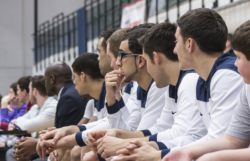 The players sit on the bench.