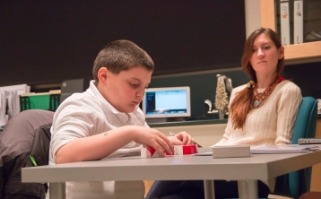 Vinnie Apicella, 9, of East Haven, demonstrates one of the testing procedures that participants would use for autism research while Whitney Hoffmann, graduate student watches on in the background.  Southern's Psychology Department has been performing autism research, centered on language difficulties, at one of their labs in Engleman Hall.
