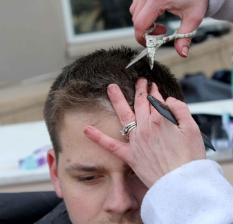 Eric Howard gets a haircut by one of the volunteer stylists for Alpha Sigma Alpha's sixth annual Buzz-A-Thon fundraiser (Photo by Aaron Berkowitz)