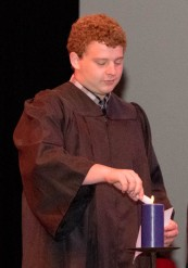 """A student lighting a candle during the """"Torch of Knowledge."""""""